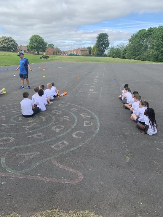 Children enjoying learning how to play cricket