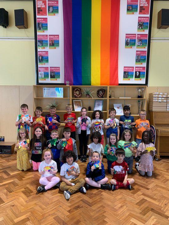 Year 2 children showing off their Elmer work under the rainbow flag