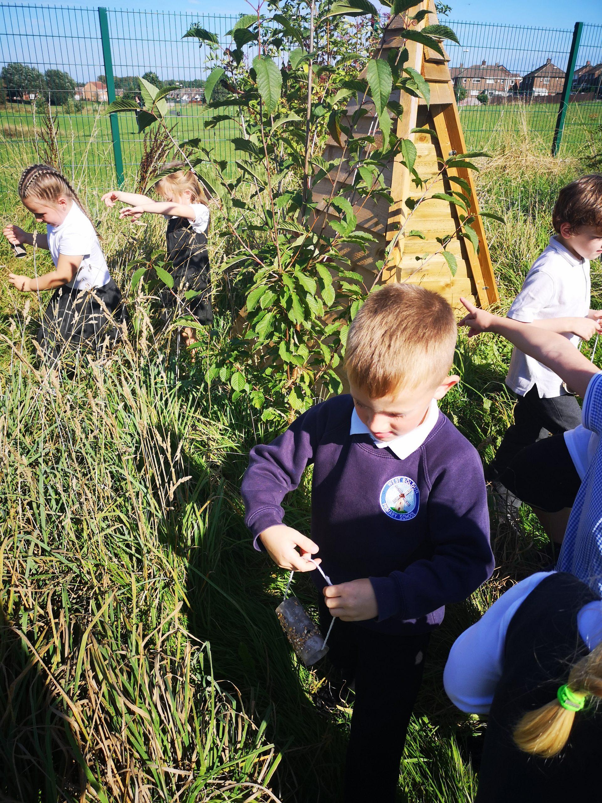 Year 1 children hanging their bird feeders